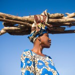 A Gambian lady, colourfully dressed in traditional clothing and fabrics, balances a heavy load of firewood on her head as she walks home in the afternoon sun. Boboi Village, Gambia.
